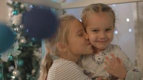 Två lyckliga små flickor leende och skratt nära julgranen stock video
