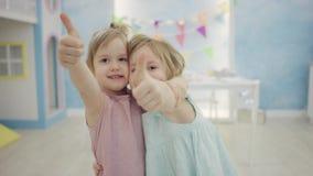 Två lyckliga små flickor som visar tummar och kramar sig som framme står av kameran lager videofilmer