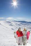 Två lyckliga snowboarders i snow räknade berg Arkivfoto
