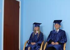 Två lyckliga studenter som sitter på stol Arkivfoto
