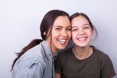 Två lyckliga systrar på grå bakgrund Royaltyfri Bild