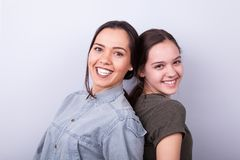 Två lyckliga systrar på grå bakgrund Arkivfoton