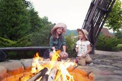 Två lyckliga systrar som grillar marshmallower Royaltyfri Foto