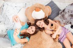 Två lyckliga systrar som ligger och tar selfie med mobiltelefonen arkivfoton