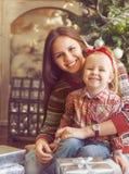 Två lyckliga systrar som sitter vid julgranen Arkivfoton