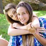 Två lyckliga tonåringflickvänner som in kramar, parkerar att se kameran Royaltyfri Fotografi