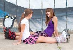 Två lyckliga tonårs- flickor i rullskridskor Royaltyfria Bilder