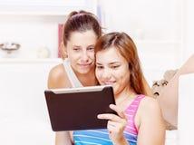 Två lyckliga tonårs- flickor som använder touchpaddatoren arkivbild