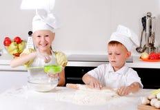 Två lyckliga unga barn som lär att baka Arkivbilder