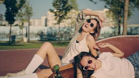 Två lyckliga unga flickor med longboarden som har gyckel tillsammans, medan sitta på skridskon, parkerar Sommarmode, fritid och stock video