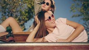 Två lyckliga unga flickor med longboarden som har gyckel tillsammans, medan sitta på skridskon, parkerar Sommarmode, fritid och arkivfilmer
