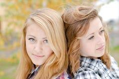 Två lyckliga teen skolar flickavänner utomhus Arkivfoton