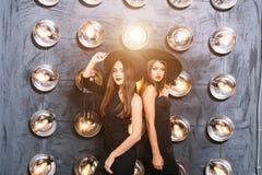 Två lyckliga unga kvinnor i svarta häxahalloween dräkter på partiet Arkivfoton
