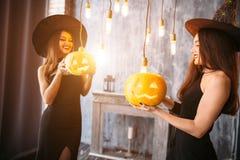 Två lyckliga unga kvinnor i svarta häxahalloween dräkter på partiet Royaltyfria Bilder