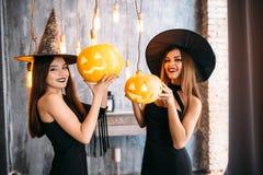 Två lyckliga unga kvinnor i svarta häxahalloween dräkter på partiet Fotografering för Bildbyråer
