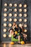 Två lyckliga unga kvinnor i svarta häxahalloween dräkter på partiet Arkivfoto