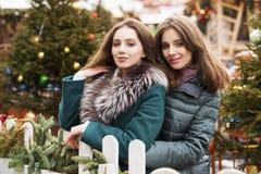 Två lyckliga unga kvinnor i vintergata, utomhus royaltyfri fotografi