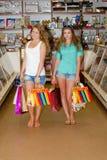 Två lyckliga unga kvinnor med shopping hänger lös Royaltyfri Foto