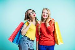 Två lyckliga unga kvinnor med shoppingpåsar på blå bakgrund ser med leende Sale, shopping, turism och lyckligt folk royaltyfri foto