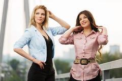 Två lyckliga unga kvinnor på bron Royaltyfri Foto