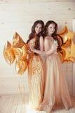 Två lyckliga unga kvinnor på partiet med exponeringsglas av champagne Cheerf royaltyfria bilder