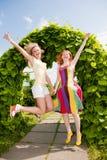 Två lyckliga unga kvinnor runing i en park arkivfoto
