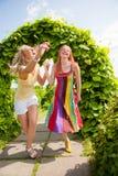 Två lyckliga unga kvinnor runing i park arkivbilder