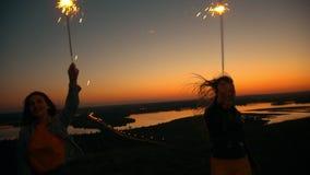 Två lyckliga unga kvinnor som dansar med tomtebloss på en kulle på sommarsolnedgången arkivfilmer