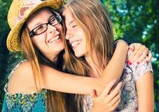 Två lyckliga unga kvinnor som kramar utomhus Royaltyfri Bild