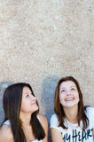 Två lyckliga unga kvinnor som ser upp på kopieringsutrymme Fotografering för Bildbyråer