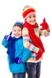 Två lyckliga ungar i vinterkläder med tummar up tecknet royaltyfri bild