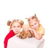 Två lyckliga ungar med den easter kaninen. Lycklig påsk Royaltyfri Bild