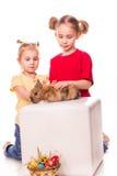 Två lyckliga ungar med den easter kaninen och ägg. Lycklig påsk Royaltyfri Bild