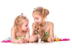 Två lyckliga ungar med den easter kaninen och ägg. Lycklig påsk Royaltyfria Bilder
