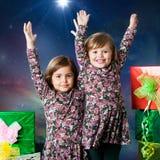 Två lyckliga ungar som lyfter händer bredvid gåvor Royaltyfri Bild
