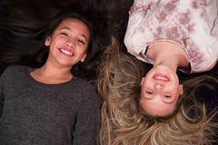 Två lyckliga ungar som ser upp från golv Arkivfoton