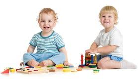 Två lyckliga ungar som spelar logiska leksaker Fotografering för Bildbyråer