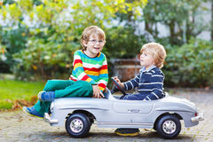Två lyckliga ungar som spelar med den stora gamla leksakbilen i sommarträdgården, ou Royaltyfri Foto