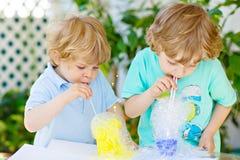 Två lyckliga ungepojkar som gör experiment med färgrika bubblor fotografering för bildbyråer