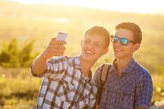 Två lyckliga vänner för gulliga grabbtagandeselfies fotograferas på telefonen royaltyfria bilder