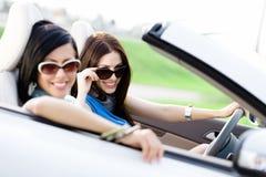 Två lyckliga vänner kör bilen arkivfoto