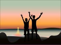 Två lyckliga vänner på solnedgången eller soluppgång på sjösidan royaltyfria foton