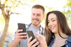 Två lyckliga vänner som använder deras smarta telefoner i a, parkerar arkivbild