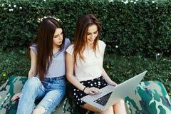 Två lyckliga vänner som direktanslutet söker i en bärbar dator som sitter på gräset i gatan arkivfoto