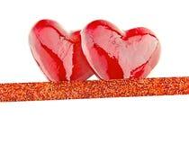 Två lyxiga röda hjärtor med bandet på vit bakgrund lyckliga valentiner för dag Blänka förälskelsekonfettier Arkivfoto