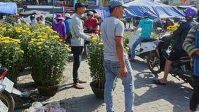 Två män Carry Large Chrysanthemum Pot i gatamarknad arkivfilmer