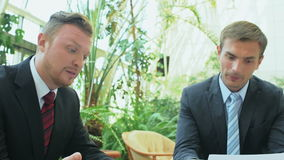 Två män diskuterar finansiellt räkna av kollegan arkivfilmer