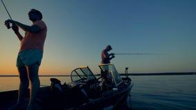 Två män ett fiske på ett fartyg i det öppna vattnet stock video