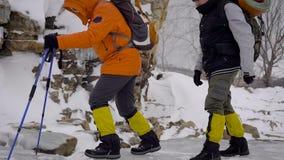 Två män gick på en vintervandring Vänner har yrkesmässig utrustning, dem promenerar klippan arkivfilmer