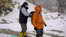 Två män gick på en vintervandring Vänner har yrkesmässig utrustning, dem promenerar klippan stock video